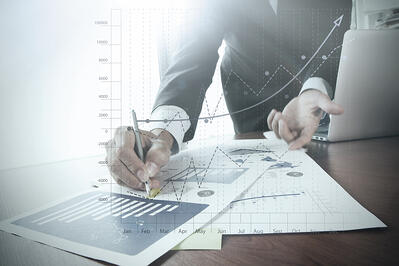 close up of businessman hand working on laptop computer with business graph information diagram on wooden desk as concept-1